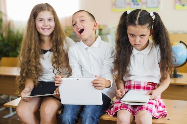 Schoolchildren sitting on desk in classroom