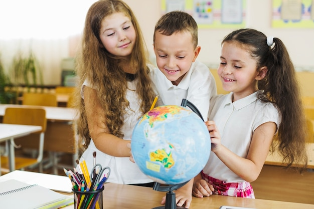 Школьники, стоящие вокруг земного шара, ставят на стол