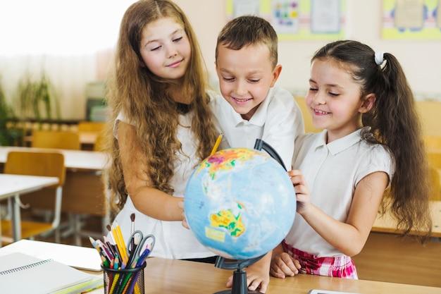 Schoolchildren standing around globe put on table