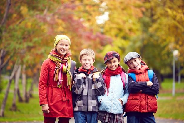 Schoolchildren with backpack after school in park