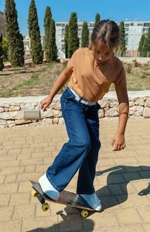 屋外でスケートボードに乗ることを学ぶtシャツの女子高生。スポーツをして公園で楽しんでいるかわいい子供。アクティブな趣味、健康的なライフスタイルのコンセプト。 tシャツのモックアップ