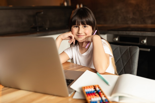Schoolgirl after online learning with a laptop. girl studies and does homework at home with a video call. distance education