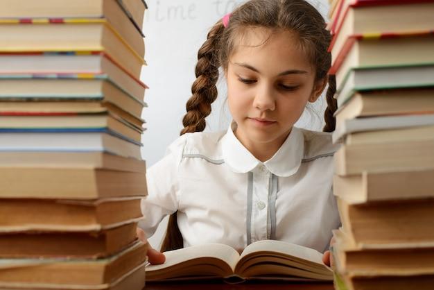 책 더미 사이의 여학생 책을 읽는 어린 소녀