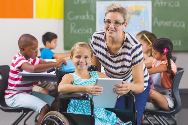 Школьница и учитель с помощью цифрового планшета в классе
