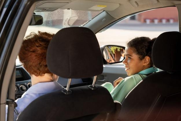 학교에 가는 길에 차 안에서 대화하는 여학생과 젊은 여성