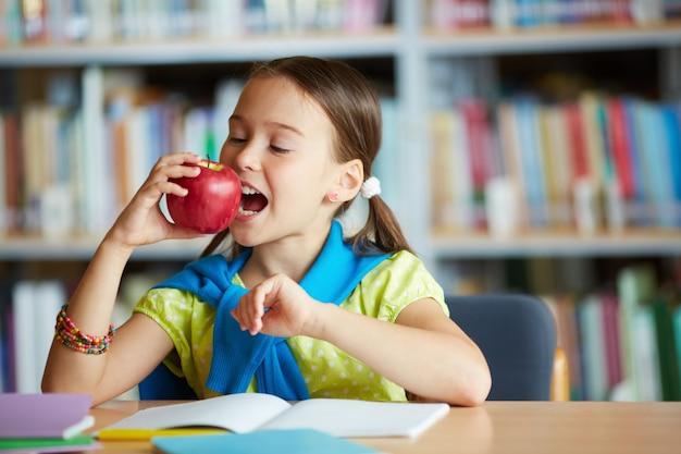 Школьница кусает яблоко в библиотеке