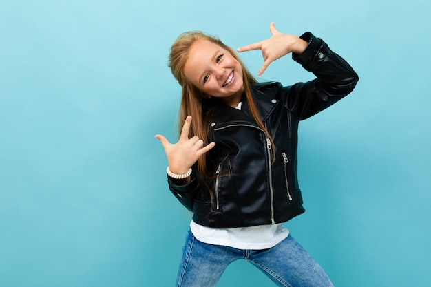 Schoolgirl in a black leather jacket is dancing on a blue background