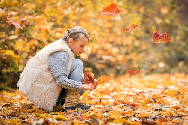 Schoolgirl collects fallen yellow maple leaves in the park.
