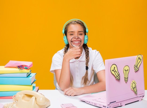 Schoolgirl on desk with laptop in memphis style