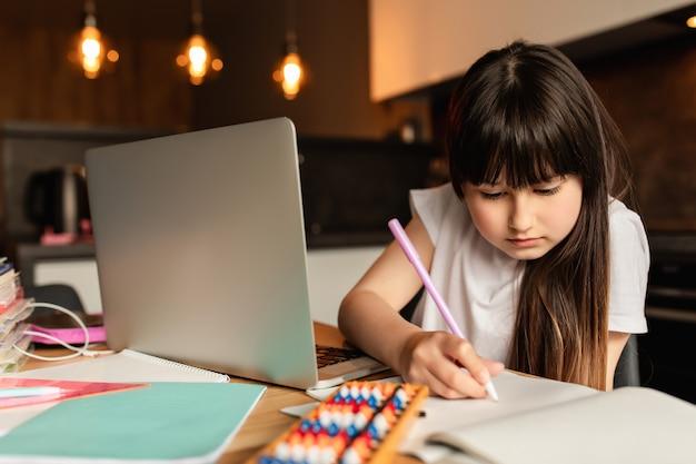 女子高生は家で宿題をします。ノートパソコンでのオンライン学習。ビデオ通話で勉強します。検疫中の遠隔教育