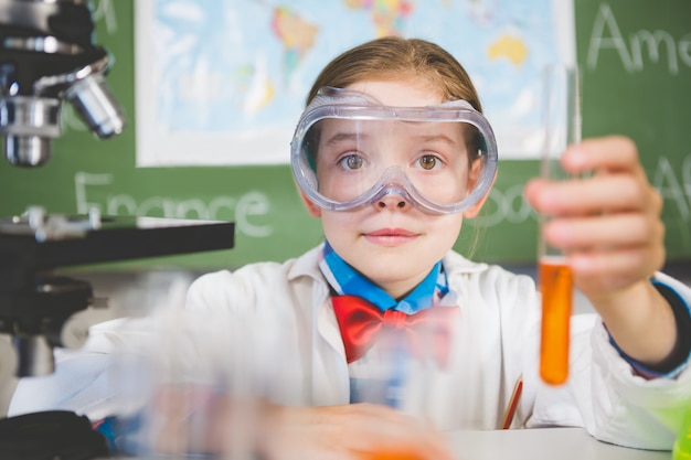 Schoolgirl doing a chemical experiment in laboratory