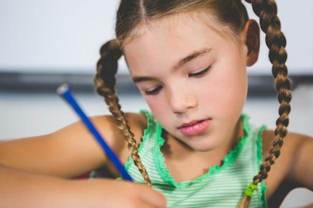 Schoolgirl doing homework in classroom