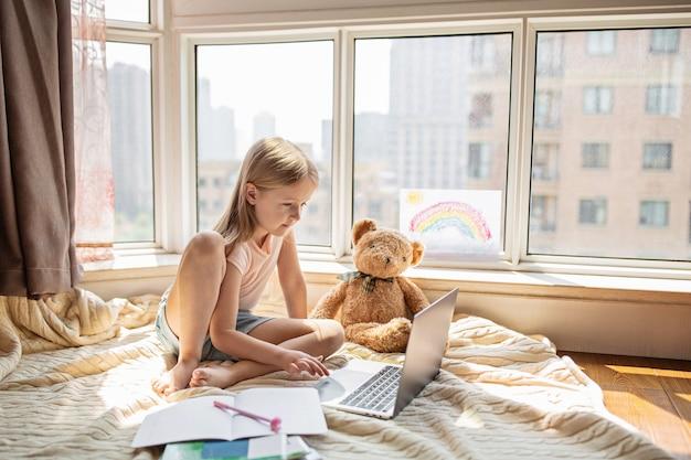Школьница делает домашнее задание во время онлайн-урока дома