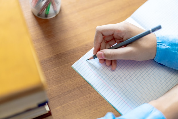 Schoolgirl doing homework with pencil on paper, back to school concept