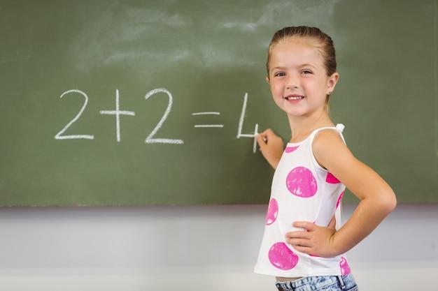 Schoolgirl doing mathematics on chalkboard in classroom