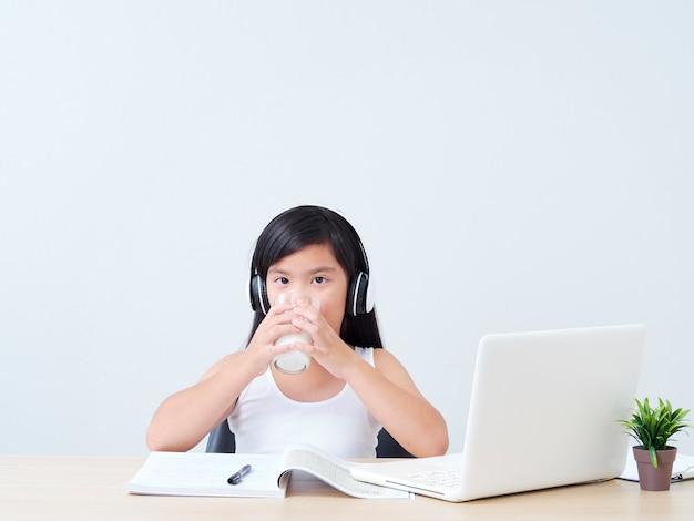 Schoolgirl drinking milk at home