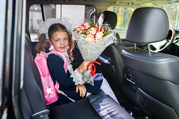A schoolgirl on the first of september is sitting in her parents ' car. dad is taking a little girl to school with a bouquet of flowers.