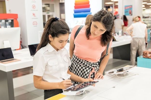 A schoolgirl girl chooses a tablet in the store
