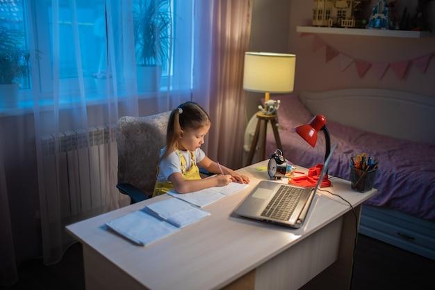 女子高生の女の子は自宅でラップトップでオンラインで勉強します。教師とオンラインで通信します。コンピュータで学校からのレッスンを教えます。遠隔教育に参加します。