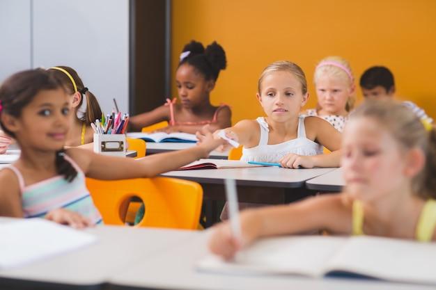 Schoolgirl giving chit to her friends in classroom
