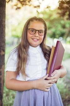 Schoolgirl in glasses standing in park holding books