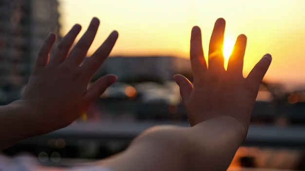 다시 일몰 빛에 여 학생 손입니다. 밝은 석양 빛 가까이에서 도시 육교 다리에 흐릿한 금속 난간을 통해 소녀 팔