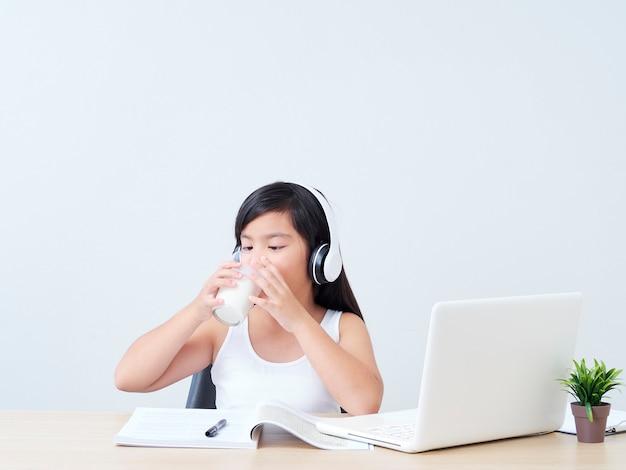 Schoolgirl in headphones drinking milk