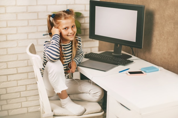 A schoolgirl in headphones sits at a table near a computer at home and does homework