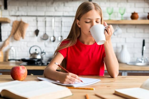 Школьница, держа чашку делать домашнее задание на кухонном столе