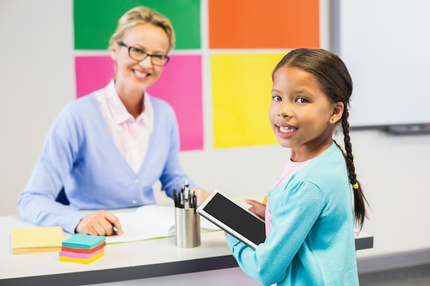 Schoolgirl holding digital tablet in classroom