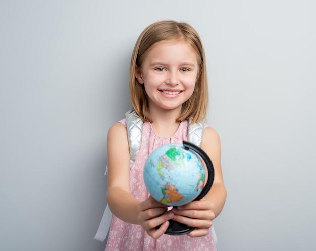 Школьница держит глобус перед ней
