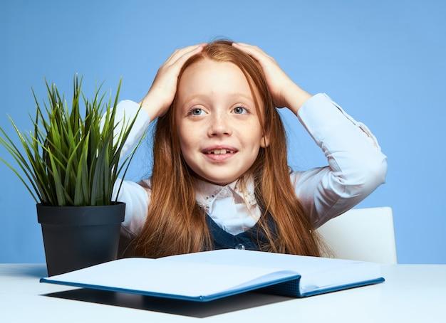 Школьница держит голову дома уроки, изучая эмоции