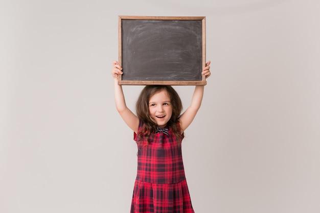 Schoolgirl holding a school board
