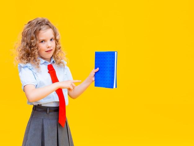 女子高生は開いた青いメモ帳を持っています。黄色の背景に分離された長い三つ編みの瞳孔。