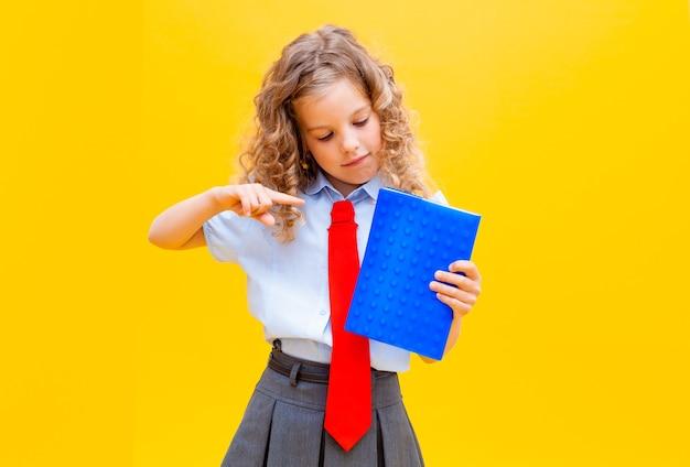女子高生は開いた青いメモ帳を持っています。