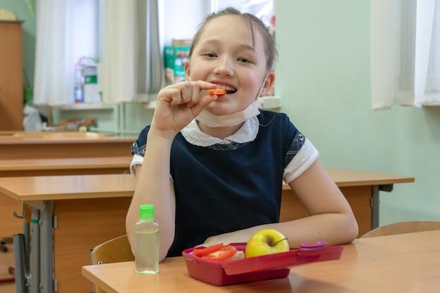 女子高生は学校の教室で手を消毒するために彼女の手で防腐剤を保持します