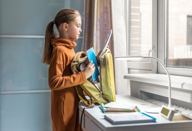 Schoolgirl at home is going to school. child collects a backpack. back to school. preparation for school.