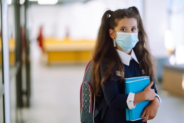 Школьница в защитной маске с рюкзаком и учебником.