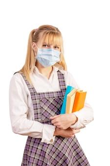 Школьница в защитной медицинской маске с учебниками в руке на белом фоне.