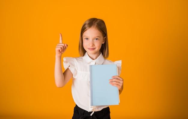흰 블라우스를 입은 여학생은 파란색 공책을 들고 노란색 배경에 손가락을 가리키며 공간 복사본을 가지고 있습니다