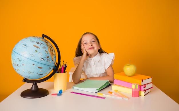 흰 블라우스를 입은 여학생이 학용품이 있는 탁자에 앉아 있고 노란색 배경에 지구본이 있는 공간 사본이 있습니다
