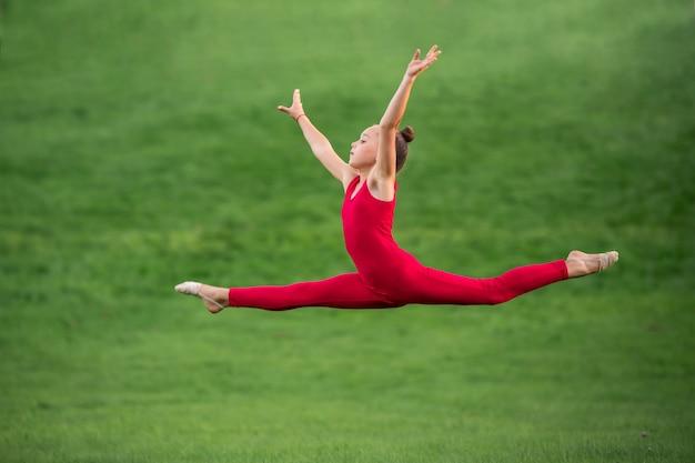 Школьница в ярко-красном комбинезоне занимается гимнастикой на траве, делая упражнения на растяжку