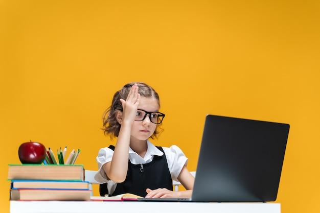 オンラインレッスンの遠方の学校の学習中にラップトップに座って手を上げる眼鏡の女子高生