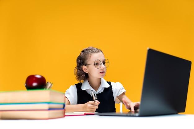 オンラインレッスンの遠方の学校の学習中にラップトップを書いたり見たりする眼鏡をかけた女子高生