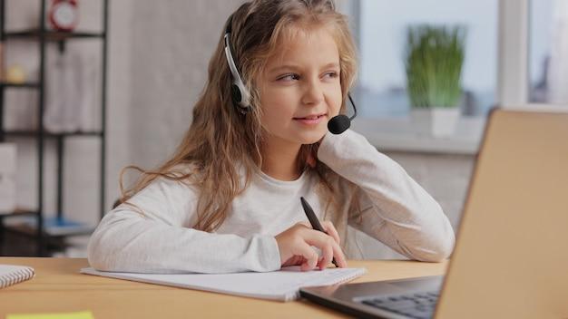 헤드셋의 여학생은 온라인 수업, 교사와의 화상 통화, 질문에 답하고 지식을 확인합니다.