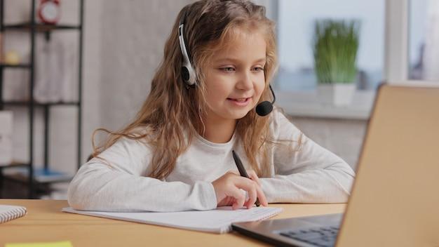 헤드셋의 여학생은 온라인 수업, 교사와 화상 통화, 노트북을 사용하여 집에서 공부하고 있습니다. 원격 교육. 가정 교육.