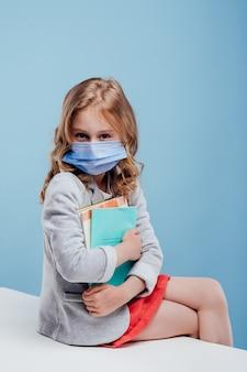 팔에 책을 안고 의료 마스크를 쓴 여학생이 테이블에 앉아 있는 카메라를 쳐다본다