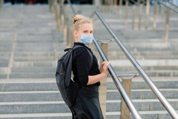 日没時の保護医療マスクの女子高生。 covid-19検疫中にバックパックを背負った現代の生徒。