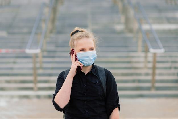 일몰에 보호 의료 마스크에여 학생입니다. covid-19 격리 기간 동안 배낭을 든 현대 학생.