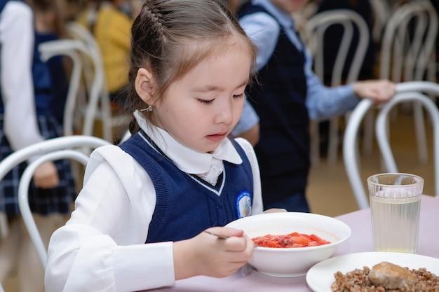 Школьница ест суп в столовой